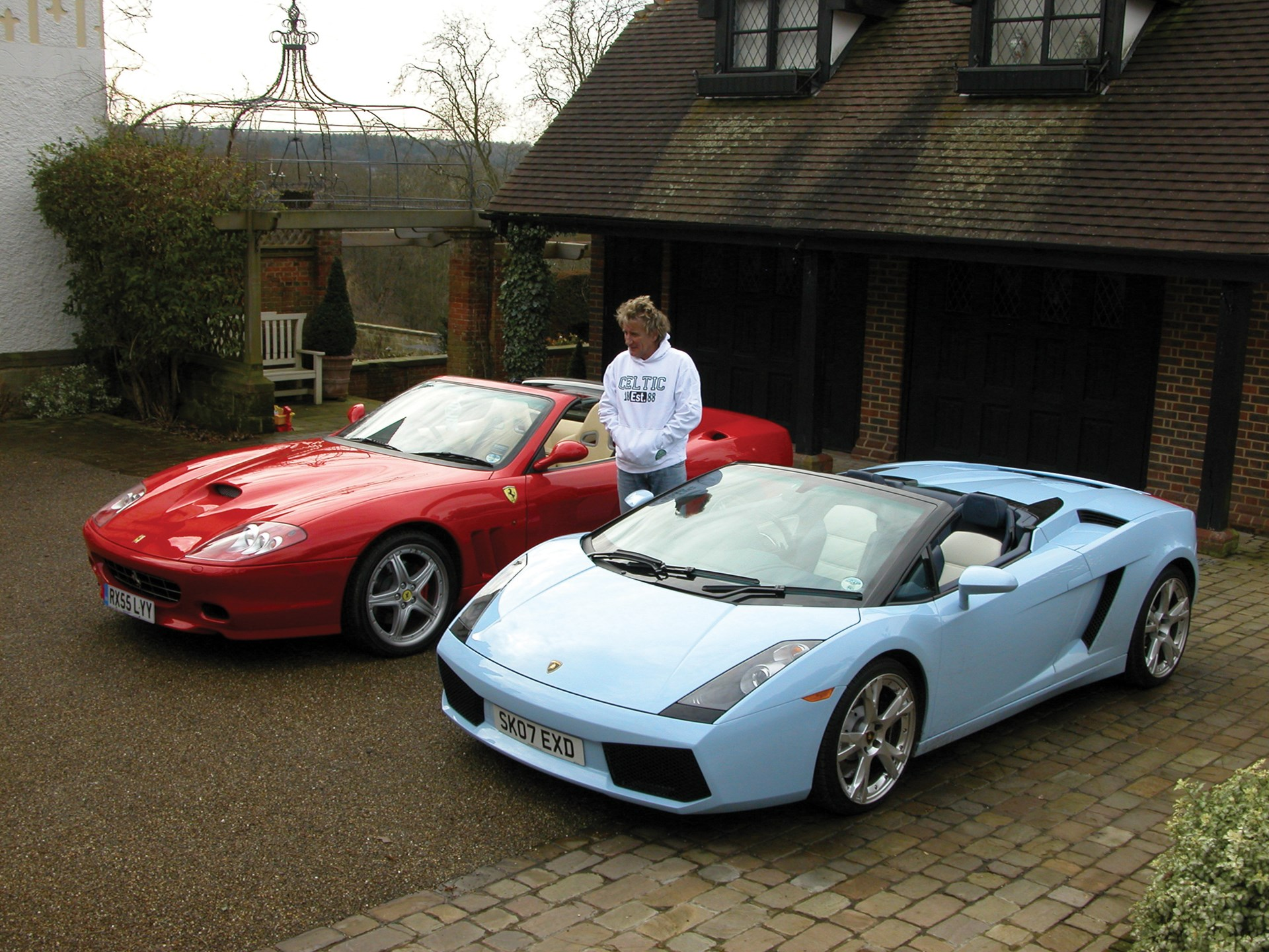 Rod Stewart poses with his Ferrari 575 Superamerica and Lamborghini Gallardo Spyder outside his home in 2009.