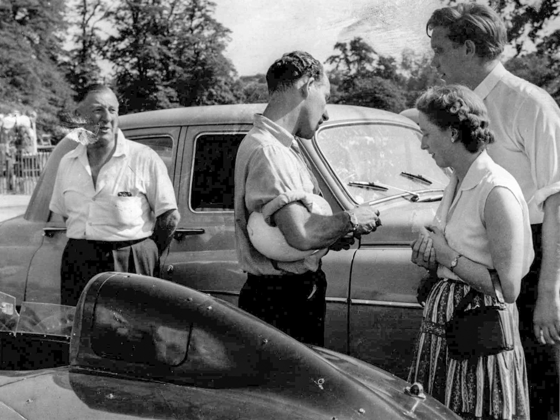 Jack Broadhead, Stirling Moss, and Bob Berry with Mrs. Berry discuss OKV 2 in the foreground.