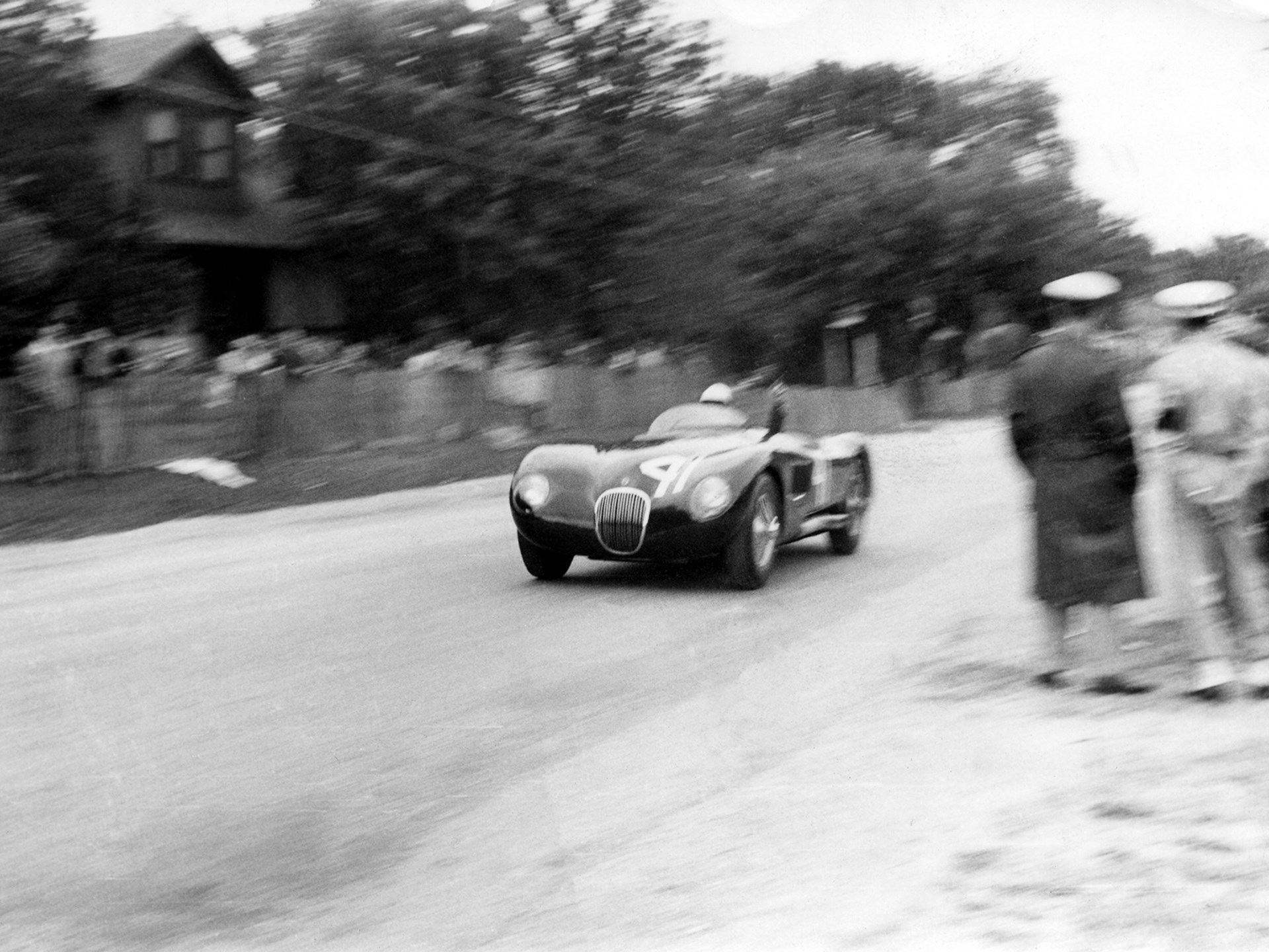 Phil Hill and XKC 007 race towards the very first victory for the C-Type in America at Elkhart Lake.