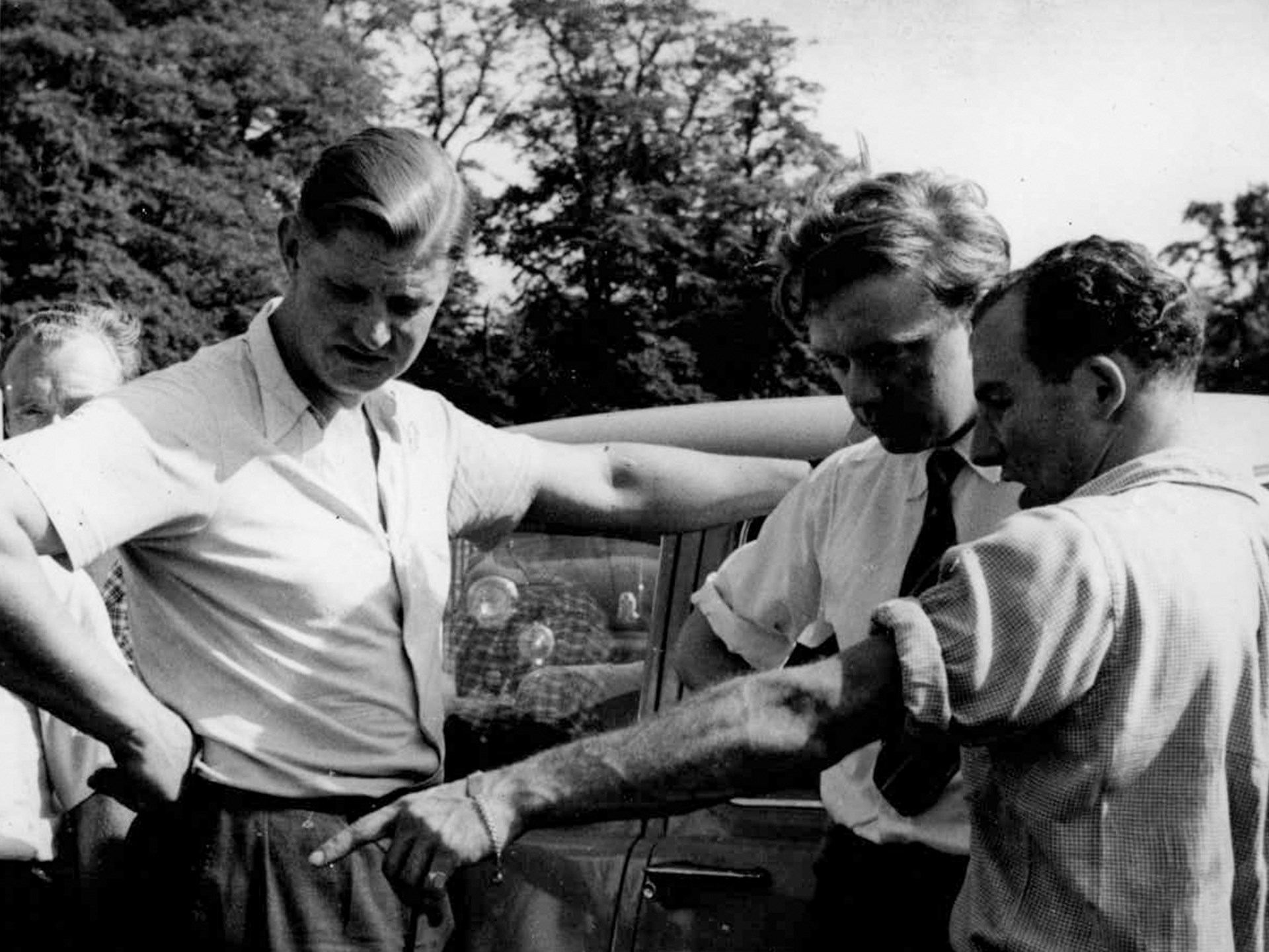 Jack Broadhead with Stirling Moss pointing out a feature of the car to Bob Berry.