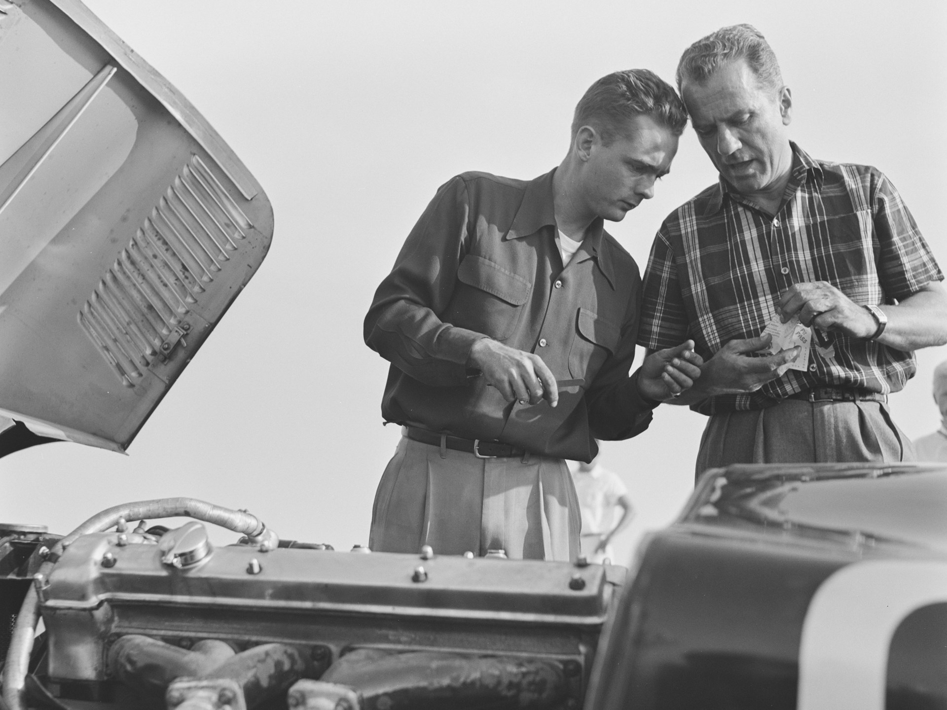 Phil Hill and a friend confer over XKC 007 in California in 1952.