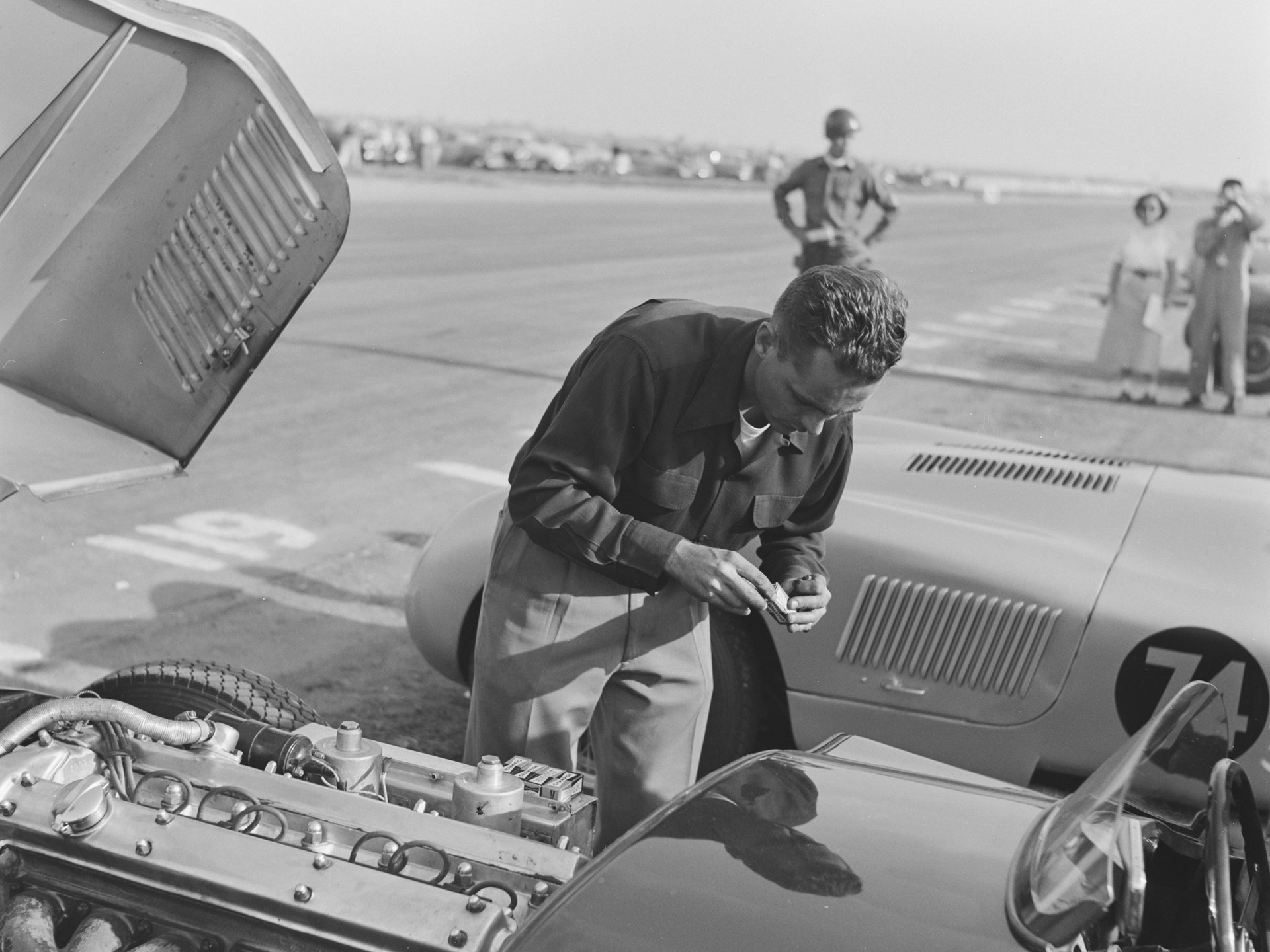 Phil Hill changes the spark plugs in XKC 007 in California in 1952.