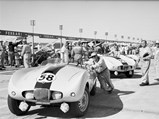 "1954 Arnolt-Bristol Bolide Works Roadster by Bertone - $Arnolt Bristol car 58 at 1955 Sebring 12 Hours race, team principal and driver ""Wacky"" Arnolt at right in racing gear; Rene Dreyfus (French driver and New York restauranteur) is in light suit with dark armband directly beyond car, just in line with our view of car's racing stripes; PHOTO BY Ozzie Lyons 1955"